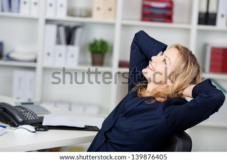 Happy businesswoman relaxing with hands behind head at office desk - stock photo