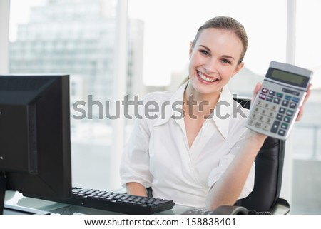 Happy businesswoman showing calculator sitting at desk in her office