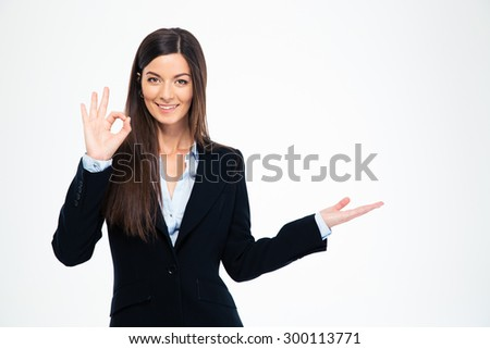 Happy businesswoman showing ok sign and holding copyspace on the palm isolated on a white background. Looking at camera - stock photo