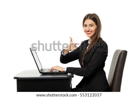 Happy businesswoman showing thumbs up sign sitting at her laptop
