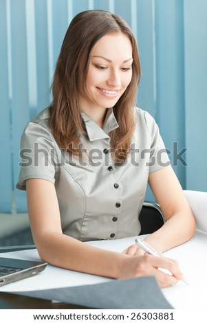 Happy businesswoman signing document at office
