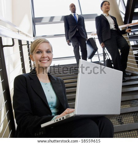 Happy businesswoman sitting and working on laptop on office stairs - stock photo