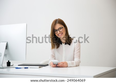 Happy businesswoman sitting at her workplace in office and holding smartphone - stock photo