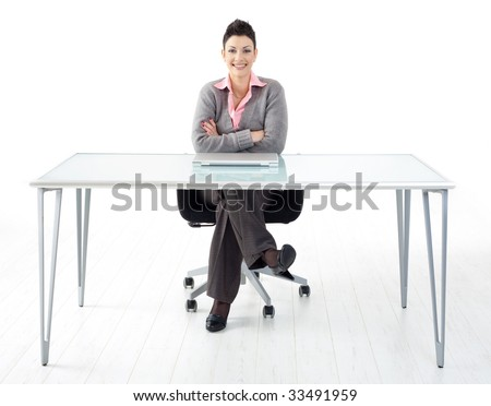 Happy businesswoman sitting at office desk, smiling. Full length portrait. Isolated on white background. - stock photo