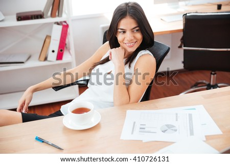 Happy businesswoman sitting at the table with coffee and looking away in office - stock photo