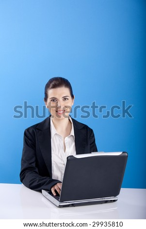 Happy Businesswoman sitting in office with a laptop