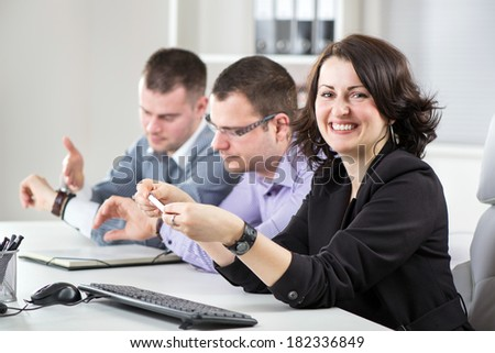 Happy Businesswoman sitting in the office. Looking at camera. His colleagues, in the background, watching the clock.