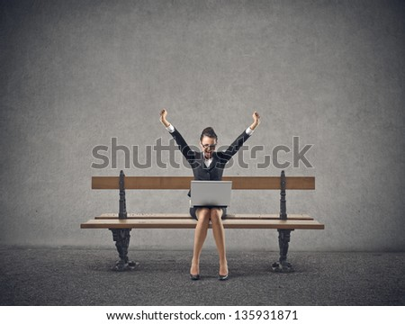happy businesswoman sitting on a bench with laptop - stock photo