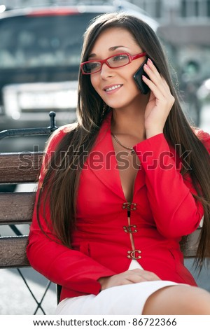 happy businesswoman sitting on bench and calling by phone - stock photo