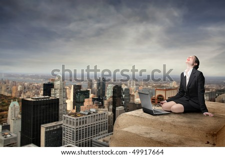 Happy businesswoman sitting on the top of a skyscraper with cityscape on the background