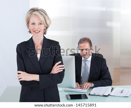 Happy Businesswoman Standing In Front Of Her Colleague Using Computer - stock photo