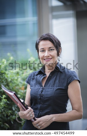 Happy businesswoman standing outside her workplace