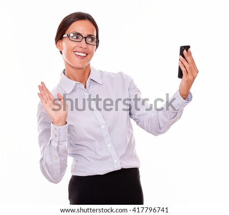 Happy businesswoman taking selfies with her cell phone with a satisfied gesture while wearing her straight hair back and a button down shirt on a white background - stock photo
