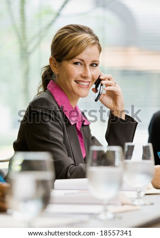 Happy businesswoman talking on cell phone in conference room - stock photo