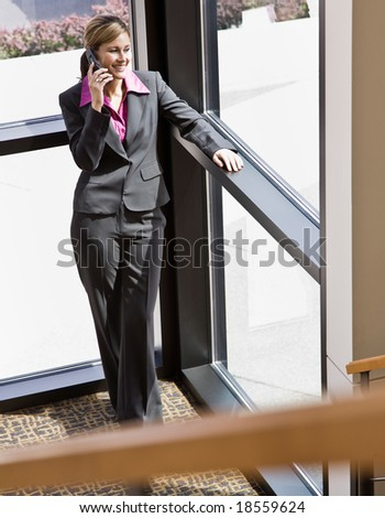 Happy businesswoman talking on cell phone in private corner of office building - stock photo