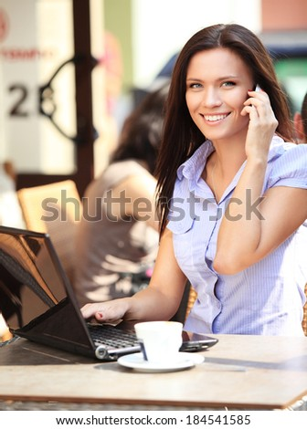 Happy businesswoman talking on the phone and using tablet computer in a coffee shop  - stock photo
