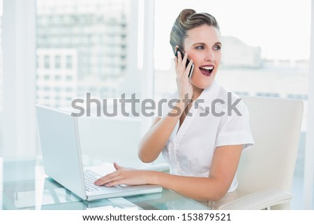 Happy businesswoman talking on the phone sitting in bright office