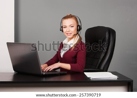 Happy businesswoman talking on the phone while working on her computer at the office - stock photo