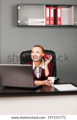 Happy businesswoman typing on laptop at her desk looking at camera in office - stock photo