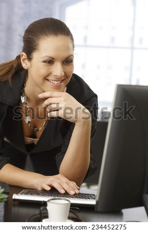 Happy businesswoman using computer in office, standing. leaning on desk. - stock photo