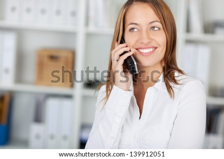 Happy businesswoman using cordless phone while looking away in office