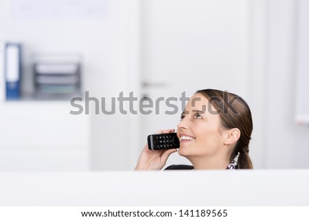 Happy businesswoman using cordless phone while looking up in office - stock photo