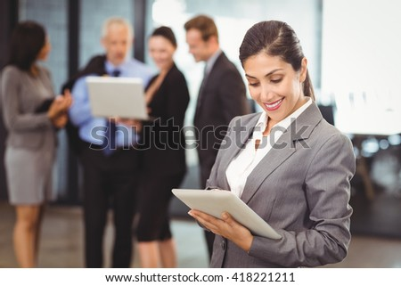 Happy businesswoman using digital tablet in office and colleagues discussing in background - stock photo