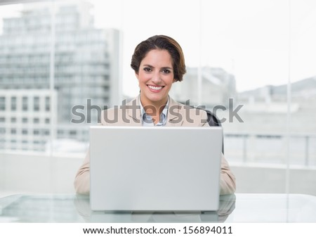 Happy businesswoman using laptop at her desk in bright office