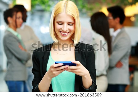 Happy businesswoman using smartphone in front of colleagues - stock photo