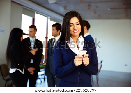 Happy businesswoman using smartphone with colleagues on background - stock photo