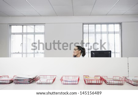 Happy businesswoman using telephone in office cubicle behind trays with documents - stock photo
