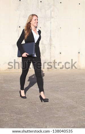 Happy businesswoman walking on the street carrying laptop