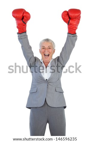Happy businesswoman wearing boxing gloves and raising her arms on white blackground