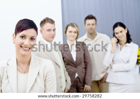 Happy businesswoman wearing glasses posing in front, looking at camera, smiling. Four businesspersons standing in the background.