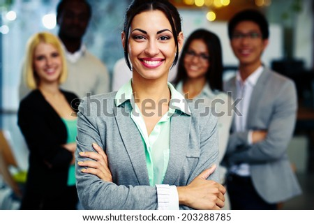 Happy businesswoman with arms folded standing in front her colleagues - stock photo