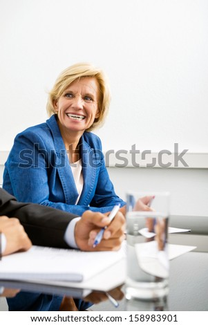 Happy businesswoman with colleague in conference room - stock photo