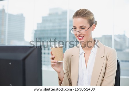 Happy businesswoman with glasses holding coffee working in bright office