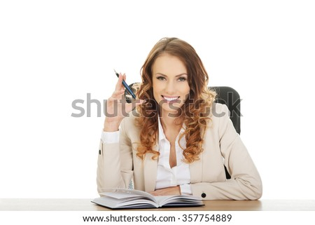 Happy businesswoman with note and pen by a desk.