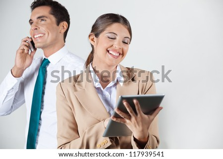 Happy businesswoman with tablet computer and manager with smartphone in the background - stock photo