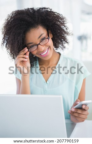 Happy businesswoman working on laptop sending a text in her office - stock photo