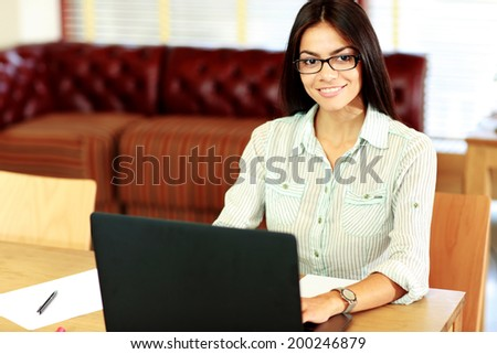 Happy businesswoman working on the laptop at office - stock photo