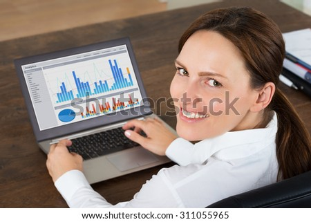 Happy Businesswoman Working With Graphs On Laptop At Desk - stock photo