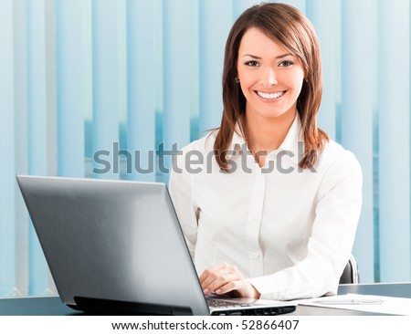 Happy businesswoman working with laptop at office - stock photo
