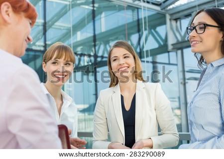 Happy businesswomen conversing in office - stock photo