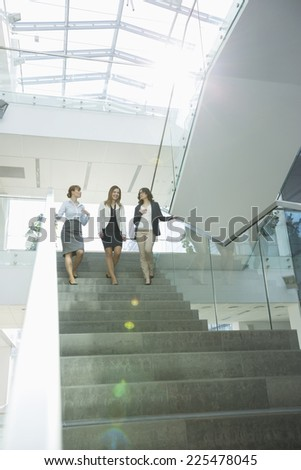 Happy businesswomen conversing while moving down steps in office - stock photo