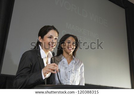 Happy businesswomen giving a lecture at podium - stock photo
