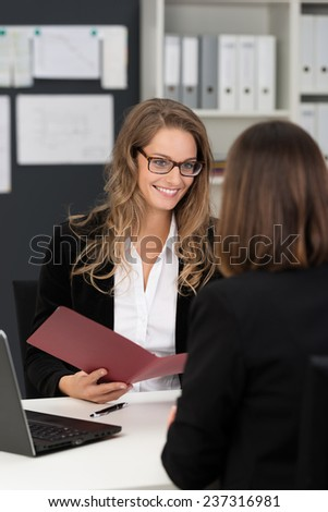 Happy Businesswomen in Black Business Coats Talking Business Reports at White Table with Computer. - stock photo