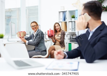 Happy businesswomen showing Christmas gifts to colleague in office - stock photo