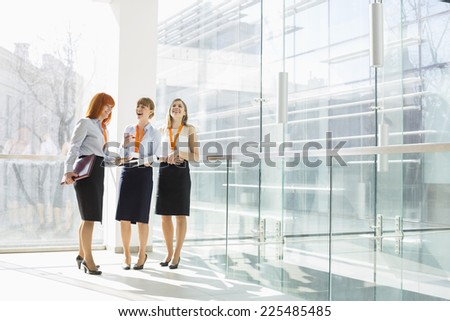 Happy businesswomen standing against glass wall in office - stock photo