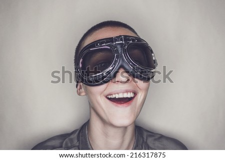 happy butch girl in retro pilot glasses over grey background